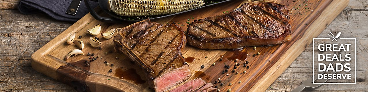 Grilled, t-bone steak and charred corn  on a wooden serving board.