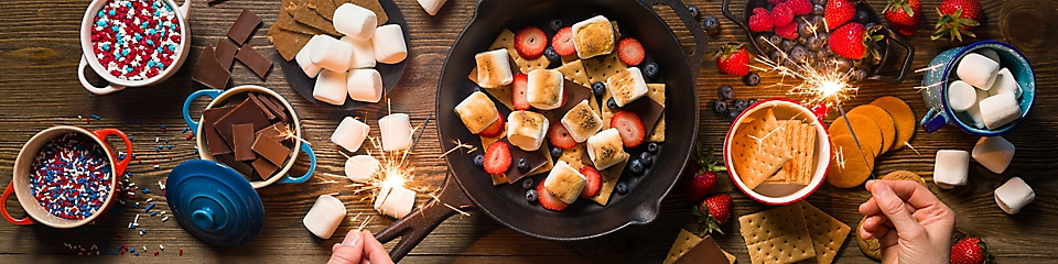 Bowls of marshmellows, graham crackers, chocolate, sprinkles, strawberries, and blueberries on a table