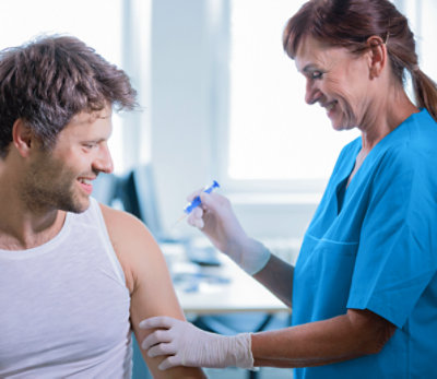 Doctor with patient and vaccine at clinic