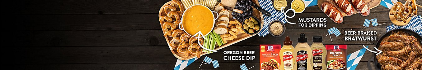 A charcuterie board with Oregon beer cheese dip, a skillet of beer-braised bratwurst, and mustards on the side for dipping.