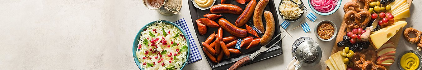 Oktoberfest food. A bowl of coleslaw, a plate of different variety of sausages, and a charcuterie board.