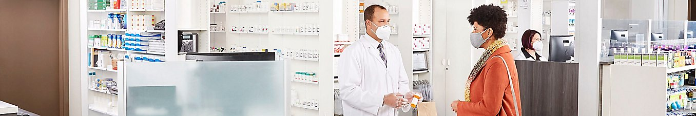 Man and woman talking to one another at pharmacy.