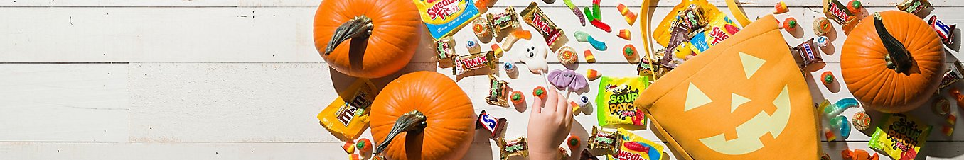 Pumpkins and trick-or-treat candies laid out on the floor